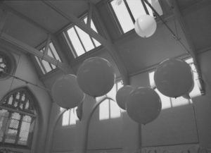 this is a grayscale image: round balloons hover at the top of a church ceiling, underneath the rafters and by the windows which let in a little light into the dusky room.