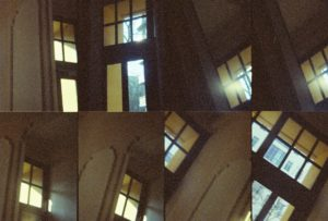 multiple frames of the same windows up at the top of the ceiling. The room is dim and the windows let in blue from the trees and golden light.