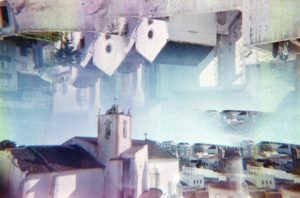 a photo of a white stucco cathedral in a city of flat white stone houses. the image is overlaid with a faint haze of the same photo flipped upside down and placed on the top (reversed). There is a purple tint to the shadows, a bluish haze to the center of the image.
