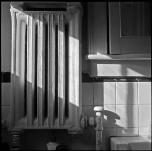 image of a bathroom radiator hanging on white tiles with a slant of sun falling across it and onto the sink.