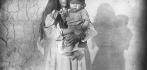 woman holding a baby. You can only see her chin and mouth and the baby in her arms. the baby is looking towards the camera.