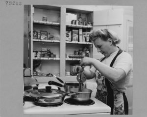 vintage image of a woman preparing a dinner in her kitchen, while wearing an apron