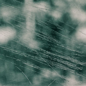 abstract image of a window with scratches and dew on it, background is green and murky and blurry.