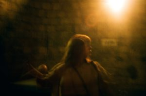 grainy image of a blurry woman under a warm orange light at nighttime outside