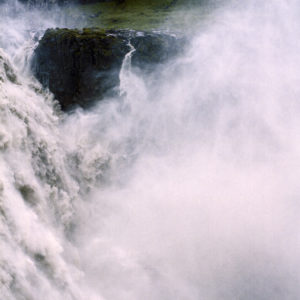 image of a large pinkish wave or spray of water crashing over a dark green rock. the image is full of the water's spray, like a thick haze you can feel.