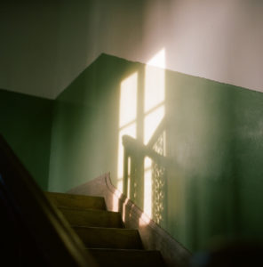 image of the shape of a window falling onto a green wall by a staircase from the sun.