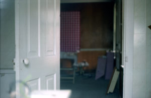 image of a white door in a pale bluish green room opening to another room that is in shadows, the windows drawn.