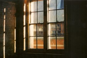 image of a window with four panes and each pane divided into four panels letting in slats of warm light into the room. the rest of the interior is in darkness. outside, you see a brick building and an orange-ish building.