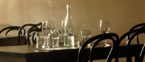 a collection of wine glasses, short and squat glasses, and a clear vase-shaped glass for water sit on top of a black table. the rims of rounded elegant black chairs sit on either side of the table.