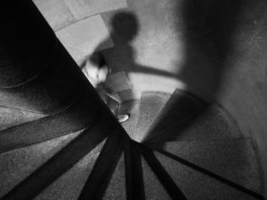 image of a woman and her shadow climbing upward a stone spiral staircase in a tower.