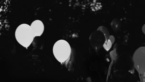 image of dusk and people holding three white balloons in the darkness by trees, the balloons are lit up and glowing slightly, everything else in the image is bathed in shadows.