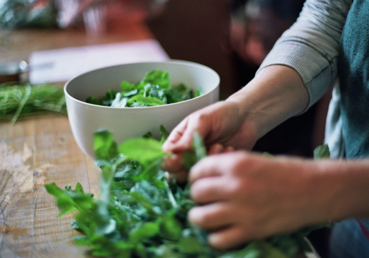 Hands plucking what looks like basil and putting it into a round white bowl on top of a wooden countertop.