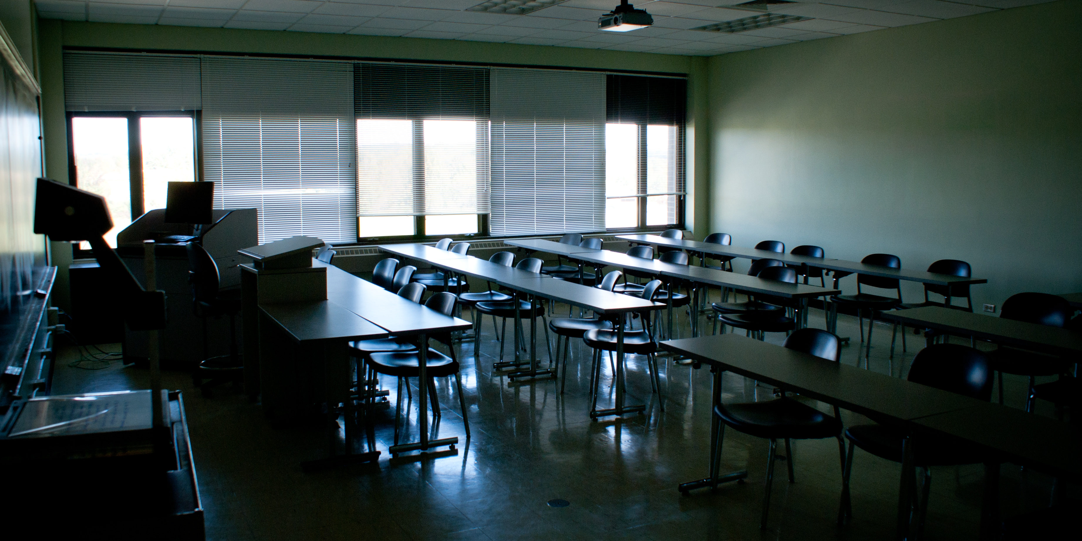 Image of an empty classroom in the mid afternoon. The room is in blue shadows with sunlight coming through the windows. The many chairs and desks are empty.