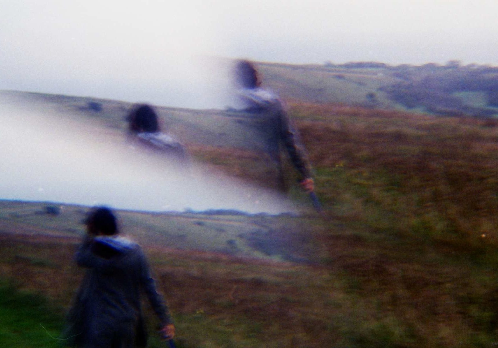 image of a woman with her back turned from the camera walking on a hill or cliff full of dry brown grass. the image has her overlaid a few times because of a film mistake.