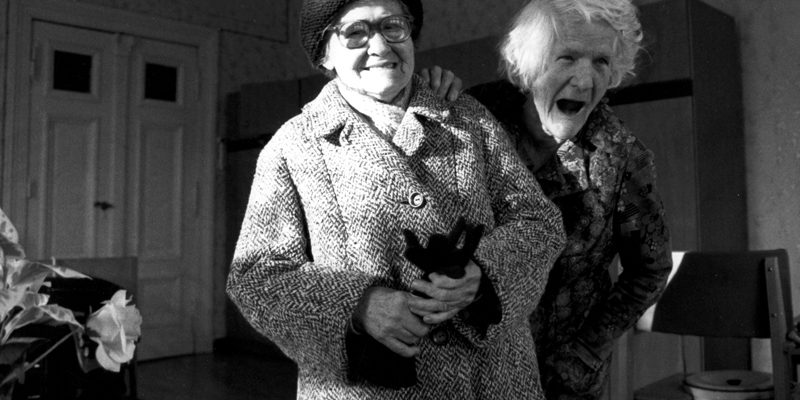 image of two old ladies in a nursing home, standing by each other and laughing. the one on the left is wearing a large coat, glasses, and has a thick woolen cap on. the one to the right stands slightly behind the other woman, and slightly in the shadows (the woman on the left is in dappled light from the sunlight from a window out of view). the woman on the right has tufts of pillowy, feathery white hair and her mouth is open in a large laugh that looks like a yawn without teeth. they stand in a room with faint wallpapering visible, a chest of drawers, and a table with a crisscross pattern near the front of the frame. the woman to the left is clutching leather gloves in her hand. they seem happy.