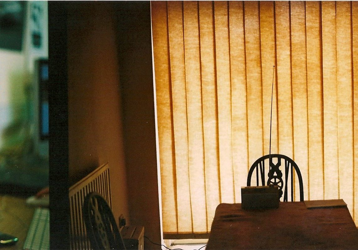 Interior of a house, a table and chair illuminated against a yellow blind behind it.