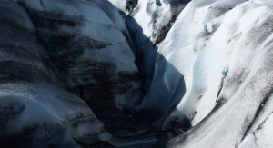 image of a large glacier shaped like a canyon with the two halves meeting in the middle like a fold in the shirt. the left side is covered in a dark blue shadow, the right side is lit by white light from the sun.