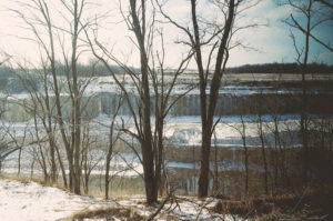 image of bare trees in front of a creek partially covered in snow.