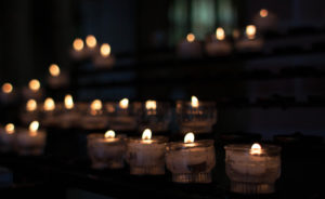 a table lined with candles in small glasses in the dark of a cathedral.