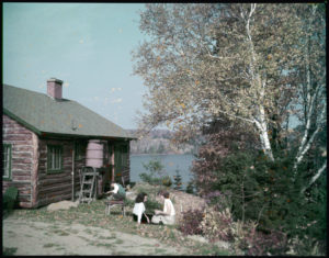 two girls sitting outside a cabin in the summertime, near a large flowering tree and in front of a lake.
