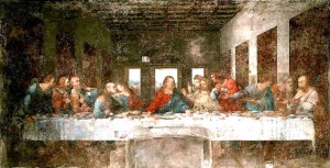 photo of Leonardo da Vinci's The Last Supper. A long white table sits in a large, well lit hall. In the center of the table, Jesus stands, leaning over the table. Around him crowd his disciples, spread and talking amongst each other.