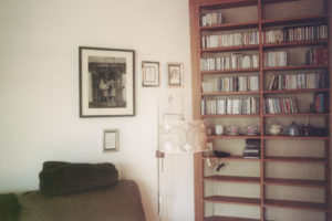 the fuzzy and blurry insides of a living room, featuring a warm wood bookshelf filled in the upper shelves with books, a floor lamp, the top of a chair, and a wall with one large framed photo and three smaller framed photos.
