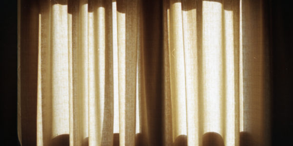 heavy overhanging curtains over a window illuminated by the sun shining through them.