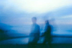 still of two blurry people in a very blue tinted image