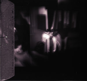 blurry image of a dark bedroom lit up by one lamp near a bookshelves on the wall