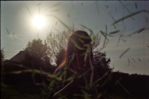 image of a woman with her face towards the camera and the sun behind her back, illuminating a large tree. she is in shadows, the hint of light on the side of her face from the light of the sun. in front of her flies grass, swirling around her in the air.