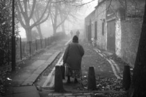 image of an old woman in a big jacket and a woolen cap on her head, turned away from the camera, walking down an old cobblestone street. to her left side is a line of trees, to her right a streak of old houses. fog smears the whole image.