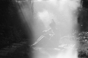 a woman sits in a clearing among trees filling a water bottle. there is a light leak across her.