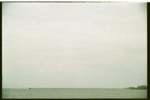 a stretch of water at the very bottom of the frame, greenish, against a pale egg colored sky, intimated to be the sea.