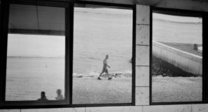 photos of three large mirrors on a wall outside, the first reflecting two people's heads at the bottom of the shoreline, the second reflecting a man walking on th beach, and the third reflecting the road to the beach.