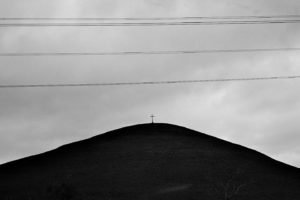 image of a small cross on top of a bare dark hill against a blank sky and underneath powerlines.