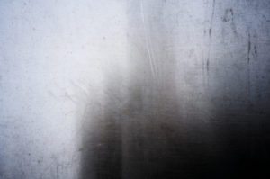 light colored metal with a dark shadowy side on the right, streaks like the shadow of a bush through a gauzy semi-opaque curtain