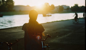 image of a woman standing with her back to the camera, in front of a bicycle. she is visible from the waist up. in front of her is a long river, and the opposite bank is full of buildings for a city. a man on a bike is in the far right distance, blurred out. the woman is lit up by a patch of golden light in an otherwise greenish blue image of dusk.