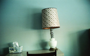 image of a white lamp and a box of kleenex in front of a bluish mint green wall. the image is slightly tilted.