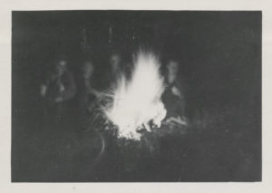 old black and white image that looks like a polaroid of a large campfire. the flames are in a warm glow in the center. behind the fire sits four blurry people, caught in mid-motion in the shadows.