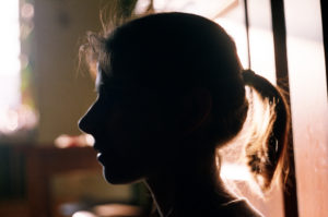 silhouette of a woman's face in a warmly lit room.