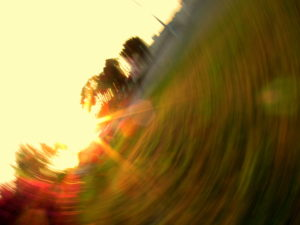 image of a field and a yellow sky and a burst of sunlight in a blurry, motion-fraught circle from a spinning camera.