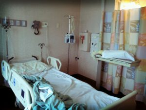 an empty hospital bed with the covers askew in a room lit by evening dusk.