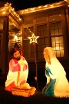 Image of inflatable Mary and Jesus statues lit up within from lights in front of a house with lights on it at nighttime.