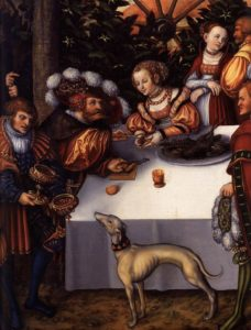 Painting of several men and women sitting around a table. The focus is on a woman in an elegant brocade who is handing the man food - she reaches across the table and cups the food in her palms that the man spears with a fork. A plate of fish bones and a goblet are also on the table. The man has a large feathered hat on and is to the left, slightly in the shadow. At his side, a man holds a large goblet to a dog that stands pointing with its nose up in front of the table. Behind the woman is dark green foliage, a spoke for a tent, and a woman in less elegant garb looking away to the right.