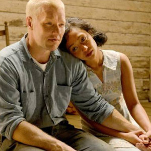 Still from the film Loving. Image shows a man and woman sitting on a porch. The woman leans her head against the man's shoulder and looks to the left. The man is looking straight ahead. They are holding hands and look concerned.