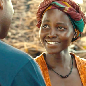 Still from the film Queen of Katwe. Image shows a young woman with a scarf wrapped around her neck looking up at a man in the foreground. She is smiling and glowing and looks hopeful.