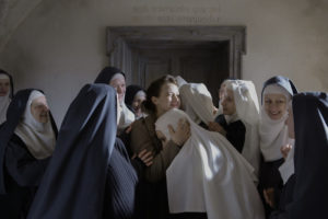 Still from Anne Fontaine's film The Innocents of a group of nuns surrounding a woman with curled brown hair who is holding a nun's head gently to her chest. They are rejoicing, the light is on their faces.