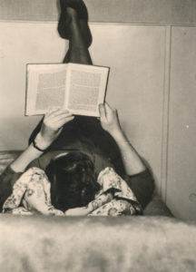 vintage photo looking down on woman lounging on floor reading.