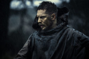 Pictured: Tom Hardy as James Keziah Delaney in FX TV series Taboo. He is in a dark rain slicker with the hood down and looking worriedly/angrily to the left.