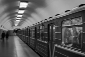 an image of a black and white subway car moving in a soft blur through a subway station.